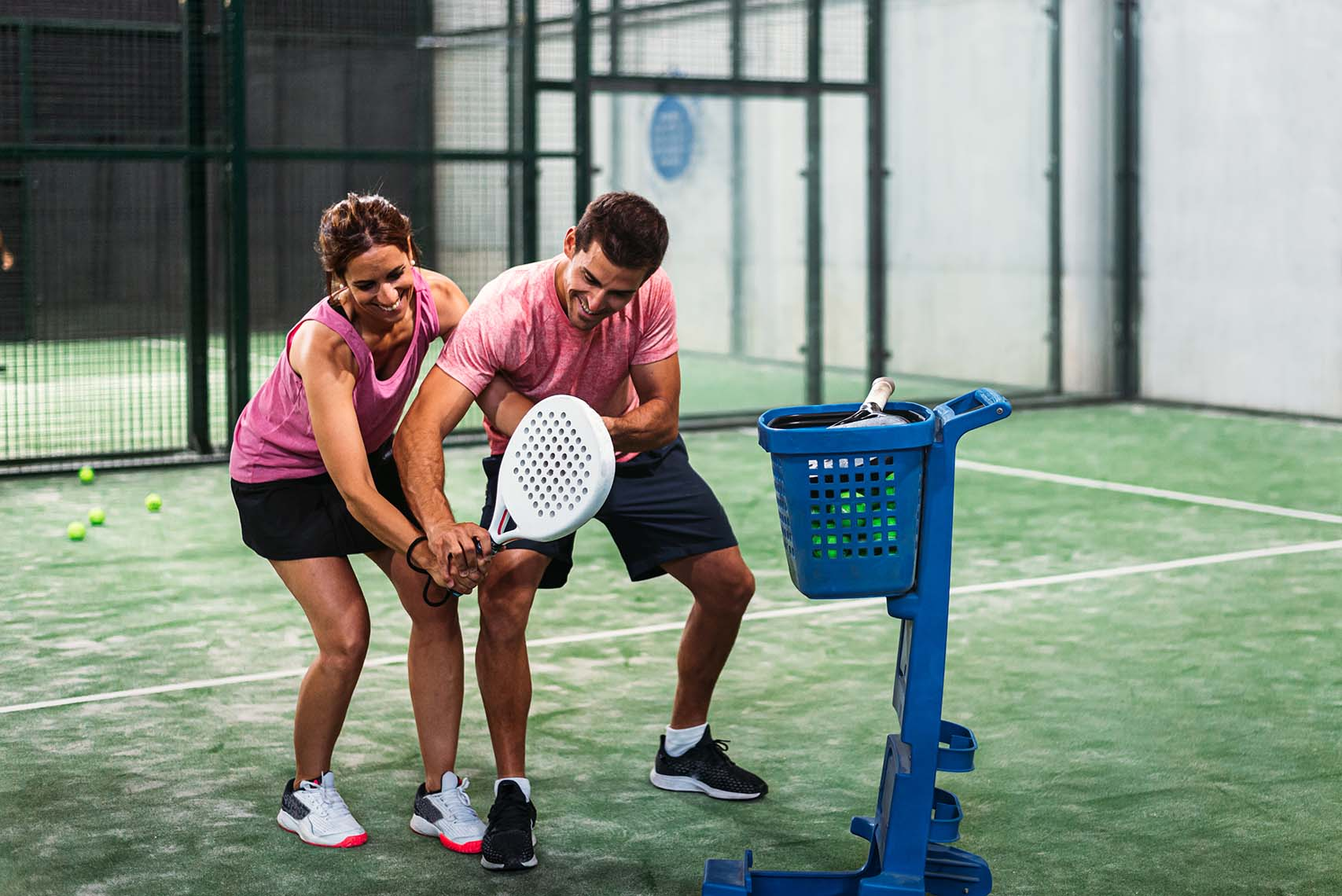 Monitor teaching padel class to woman